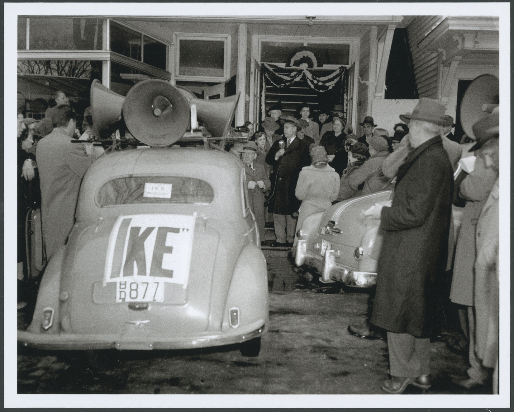 In a photograph of a street scene a man in an overcoat and hat stands near an open doorway on a sidewalk, holding a microphone and speaking to a crowd of people gathered around him. People wear raincoats, women are wearing hats or scarves over their heads, and men are wearing hats. A car parked at the curb has loudspeakers on its roof and a sign reading