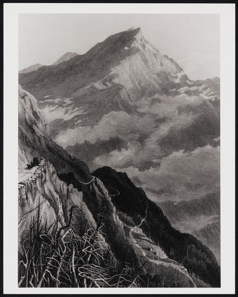 A black and white photograph shows steep rocks rising to the left in the foreground. In the distance, a large mountain is seen, rising through clouds. The peak is rocky and bare.