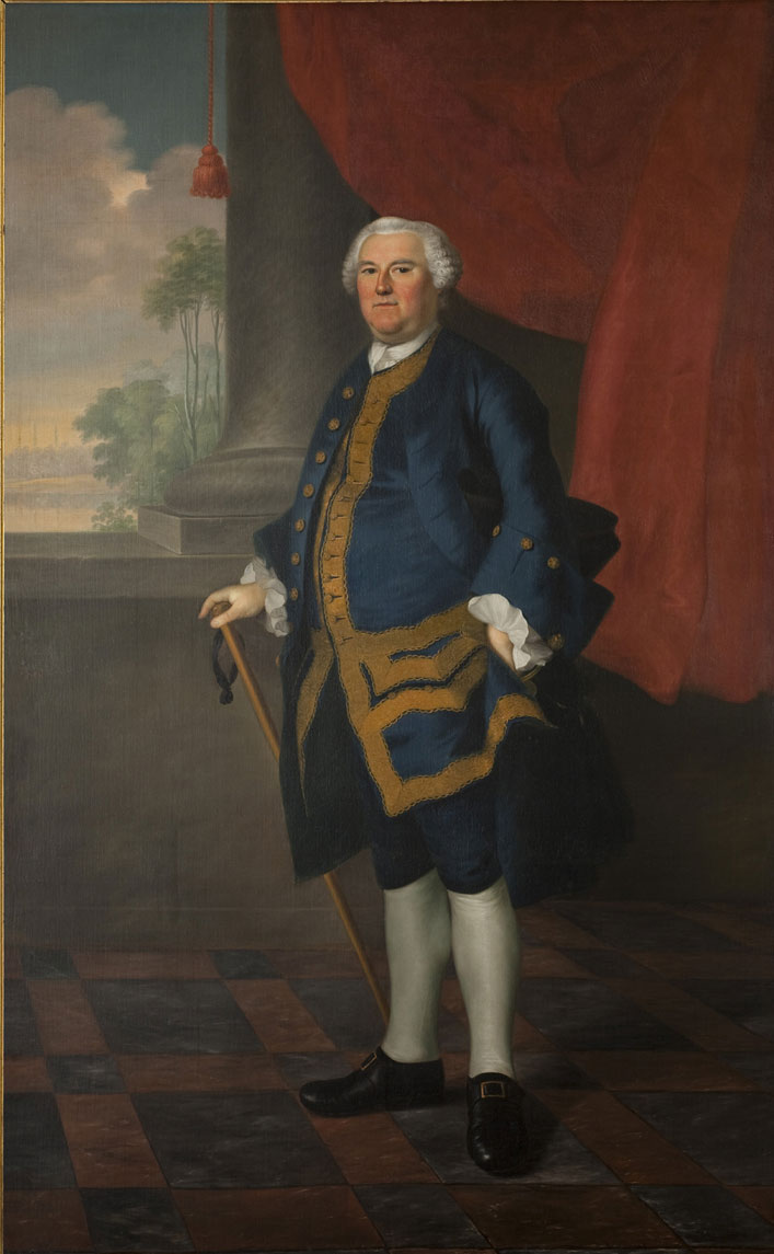 A colorful painting shows a white-haired man in formal dress posed standing with a cane. He is not smiling and looks directly at the viewer. He is wearing a long blue coat bordered with gold, a white shirt with ruffled cuffs, and knee-length blue pants. He has white stockings and black shoes with brass buckles. He stands on a black and tan checked floor in front of a column and red curtain. In the background are tall trees, clouds, and a village far away.