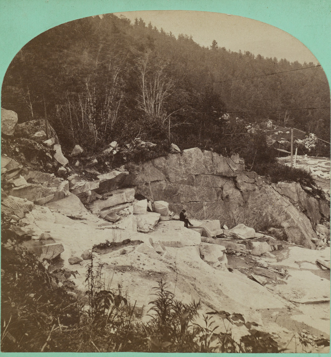 A long teal rectangle bordered with black shows two square images of the same scene next to each other. The images are black and white and arched on the top. They show the side of a hill, and the top and bottom of the image are wooded. In the middle is a wide swath of light colored rock. There are some large boulders, some slabs, and some cliff-like drops. To the left of the image, words in the margin read