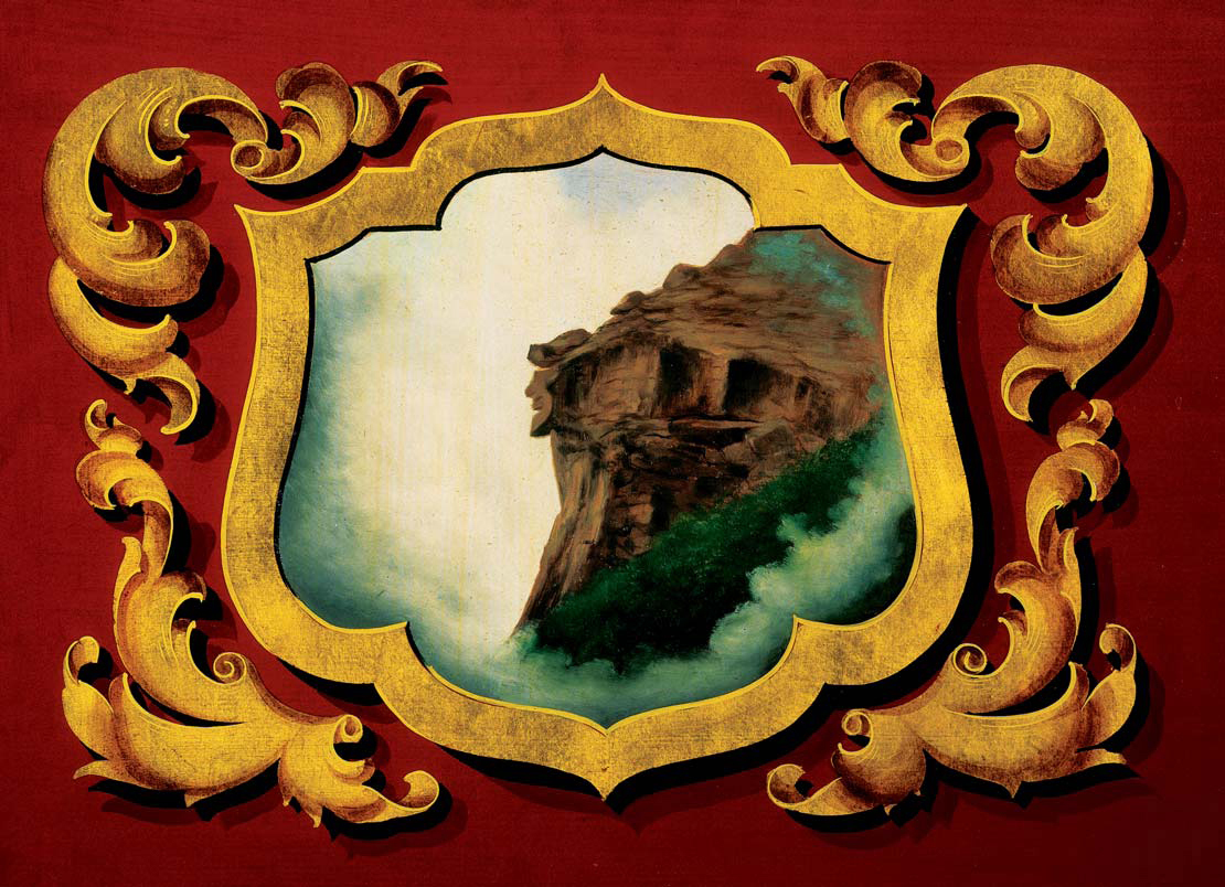 An ornate painting shows a picture framed by gold decorations with red background. The picture shows the side of a mountain, and the upper third of the rocky cliff appears to look like the profile of a man.