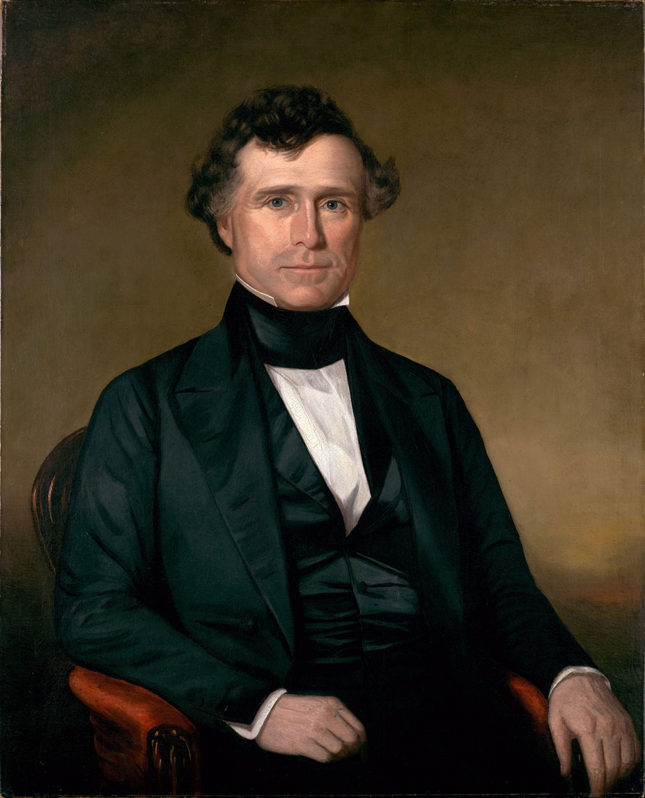 In a color painting, a man sits on a leather chair against a brown background. He is wearing a black suit in the mid-1800s style with high collar and no tie. His hands rest on the arms of the chair in a casual manner, and he looks directly at the viewer with a small smile. He has short curly brown hair and no facial hair.