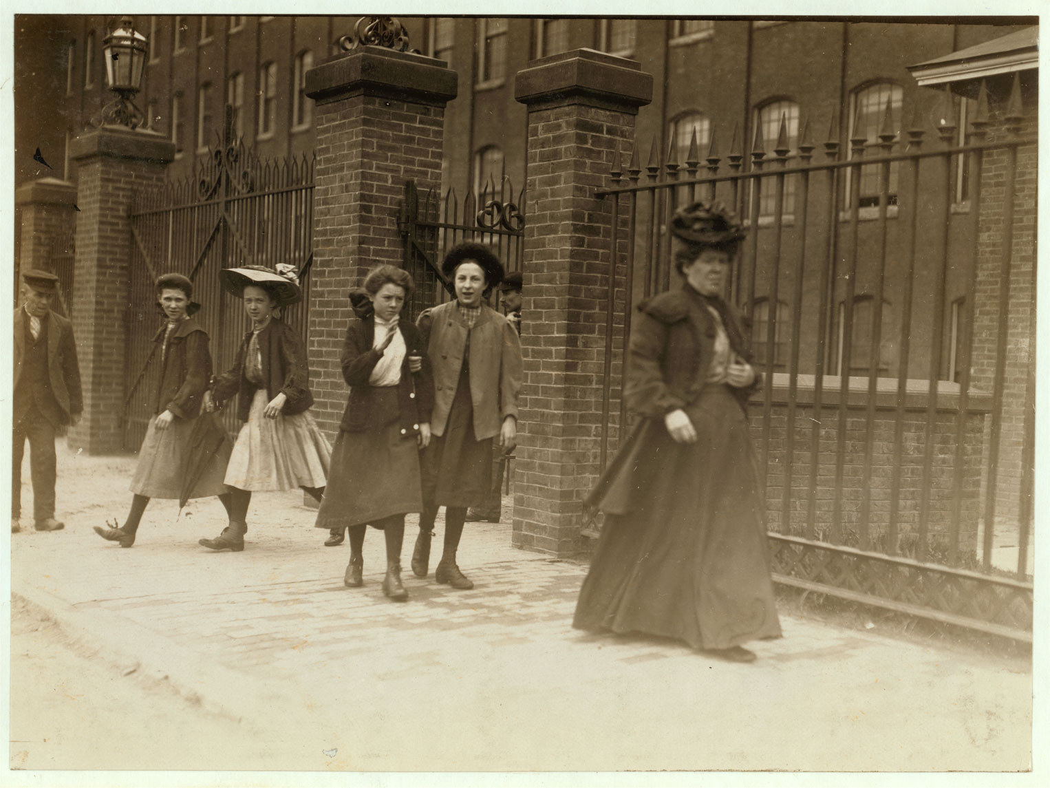 In a black and white photograph, the outside of a brick building is shown. Wrought-iron gates with tall brick columns fence the building. People are exiting through the gate out to the dusty sidewalk. One women wears long dark skirts, a formal jacket, and a decorative hat. Behind her, four girls just leaving the gate wear shin length skirts, jackets, and hats or bows in their hair. One man wears a dark suit and a casual hat and is watching them all leave.