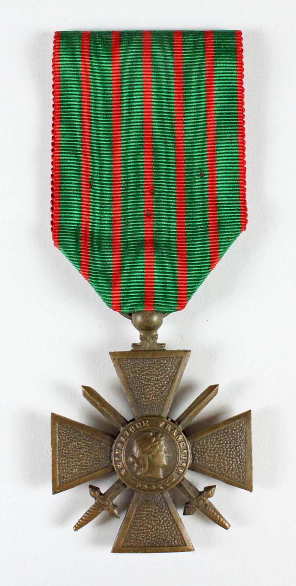 A bronze medal hangs from a wide, green ribbon with narrow red vertical stripes. The medal has an equal-armed cross with crossed swords. There is a medallion in the center with a head in profile and the text