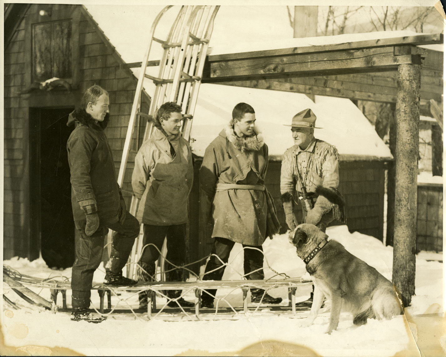 A black and white photograph shows four men and a dog outside. The four men are talking together, and wearing winter outdoors clothes. One man has a hat with a broad rim all around. The dog is sitting looking at the men. There is a barn and lean-to in the background as well as two toboggins. One toboggin is lying in front of the men and one man has his foot on it; the other toboggin is standing up against the lean-to behind them.