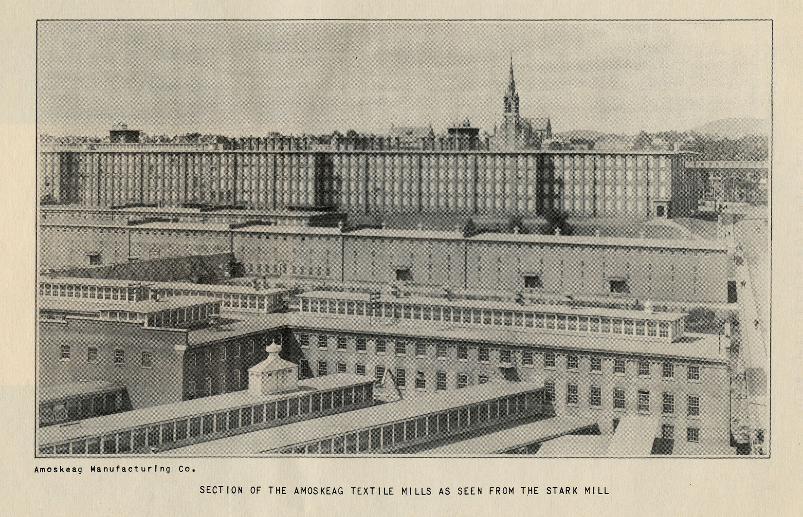 A black and white photograph shows many mill buildings from a high perspective. In the foreground, they run horizontally and vertically, and in the background there is one long factory building. Behind and on the sides of the buildings, the surrounding town can be seen. The caption reads