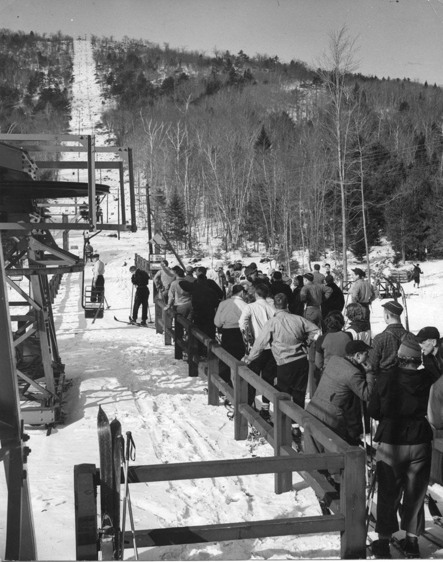 A black and white photograph shows a small mountain in the winter. Up the mountain runs a wide, white trail as well as supporting posts and wires for an old chair lift. In the foreground, people in winter clothes line up along a fence. The viewer can see one person getting ready to board the next chair that is coming.