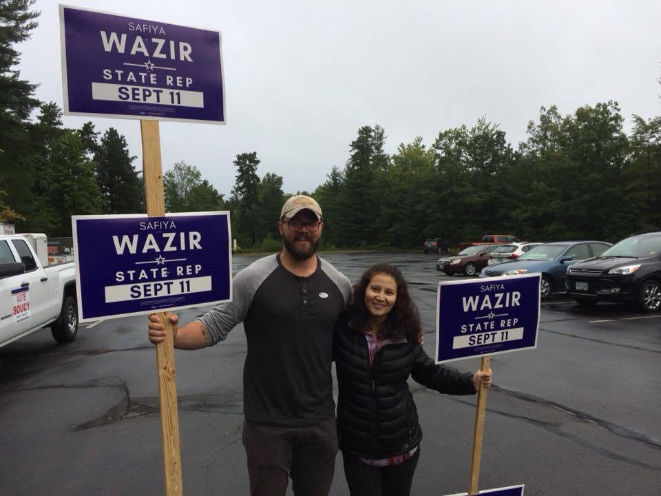 "Two people stand in a parking lot in a color photograph. A woman wears a black jacket and smiles, and a smiling man wears a cap, and casual pants and shirt. He holds two signs that are the same stacked on each other on a wooden pole, and she holds one of the same sign. The signs read ""SAFIYA/ WAZIR/ STATE REP/ SEPT 11."""