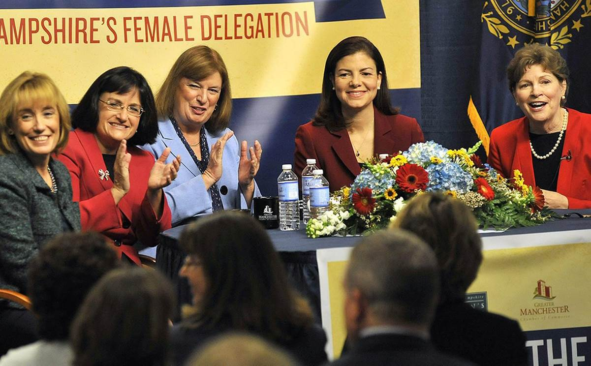 In a color photograph, five women sit at a table wearing suits, all facing an audience. Two are clapping and all are smiling. On the table in front of them is a large arrangement of flowers and some water bottles. Behind them are the words