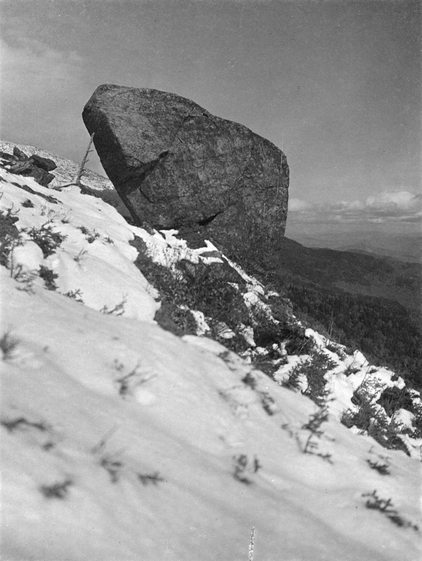 On a snow-covered steep hill a large, irregularly-shaped boulder sits perched in this photograph.