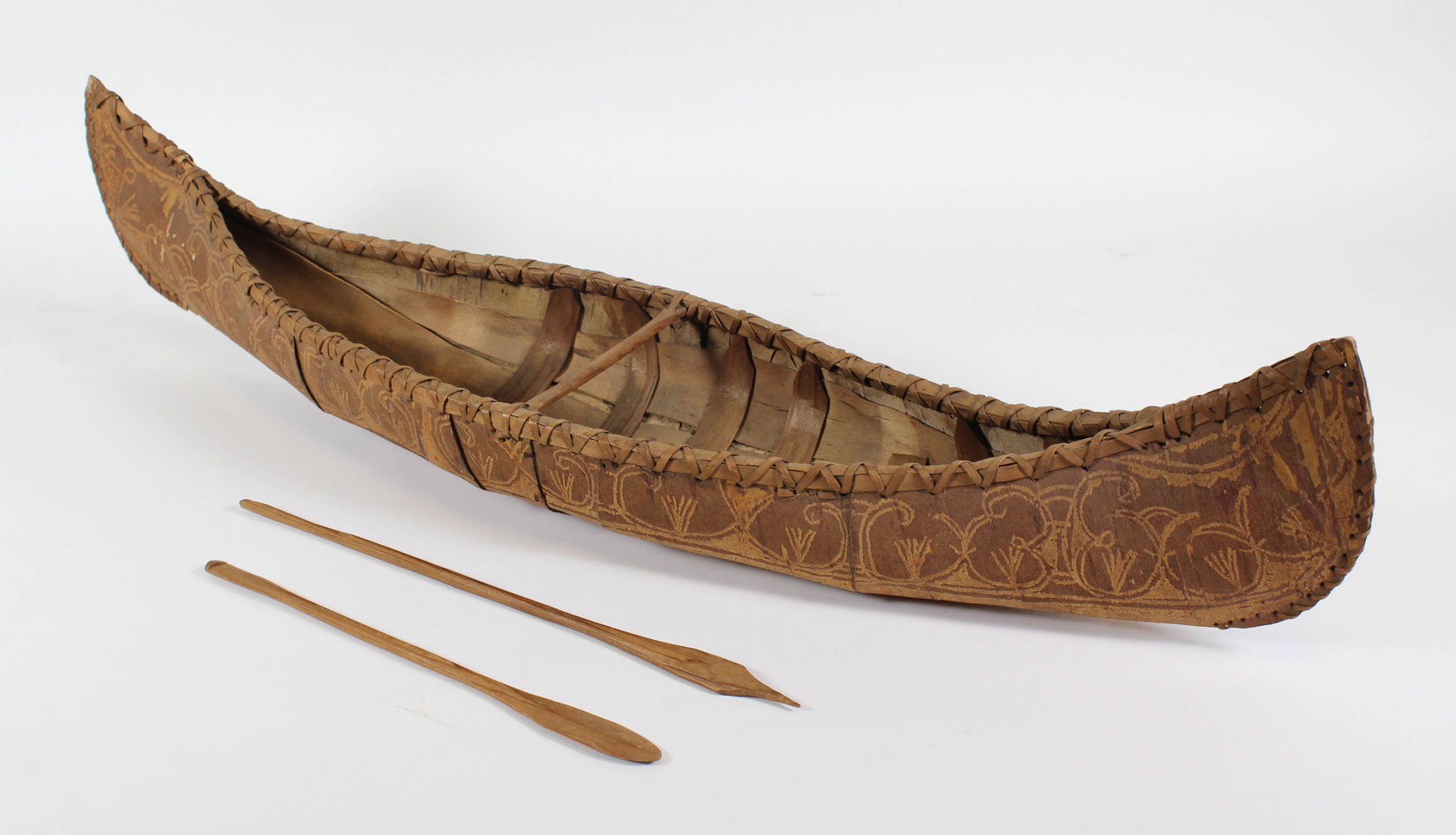 A model of a birchbark canoe has brown birchbark on a wooden frame. There is one thwart in the center. Intricate double-curve designs are on the outside of the canoe. Two wooden paddles lie beside the canoe, one with a rounded blade and one with a pointed blade.
