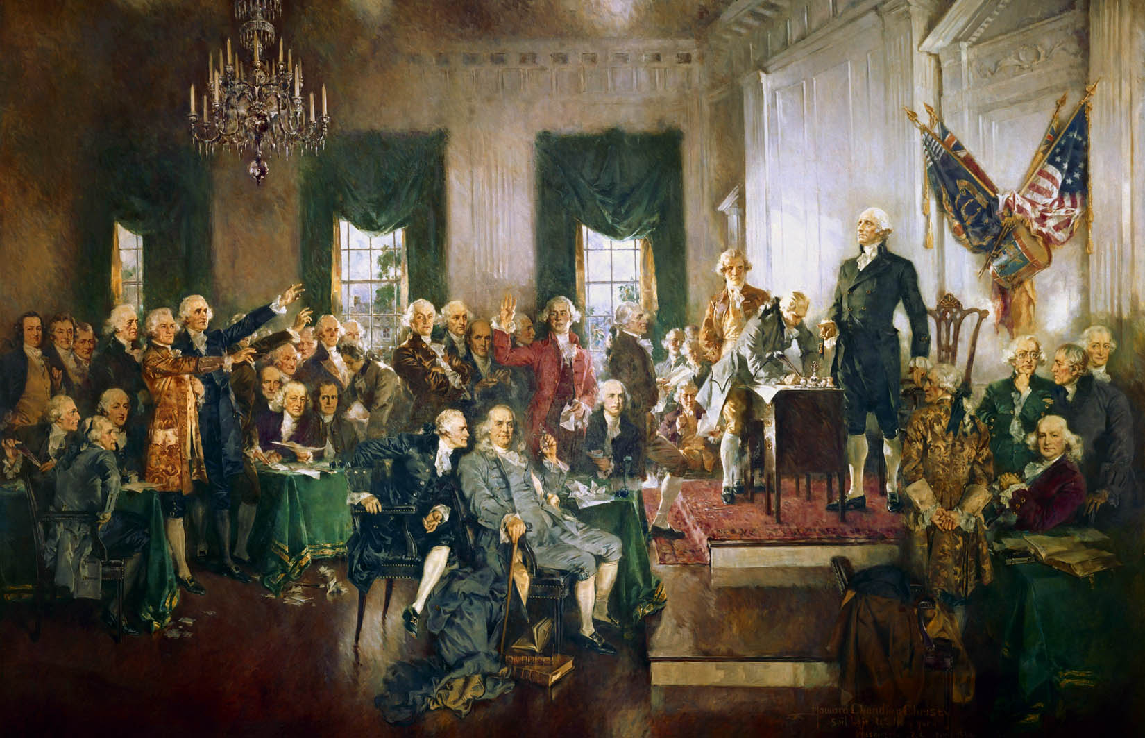 A crowd of men sit and stand in a formal room with a chandelier and fancy window treatments. They are dressed in formal suits from the 1700s. They face a dais with a desk, where one man stands in front of a chair. Another man appears to be writing on something on the desk. Flags decorate the wall behind the standing man.