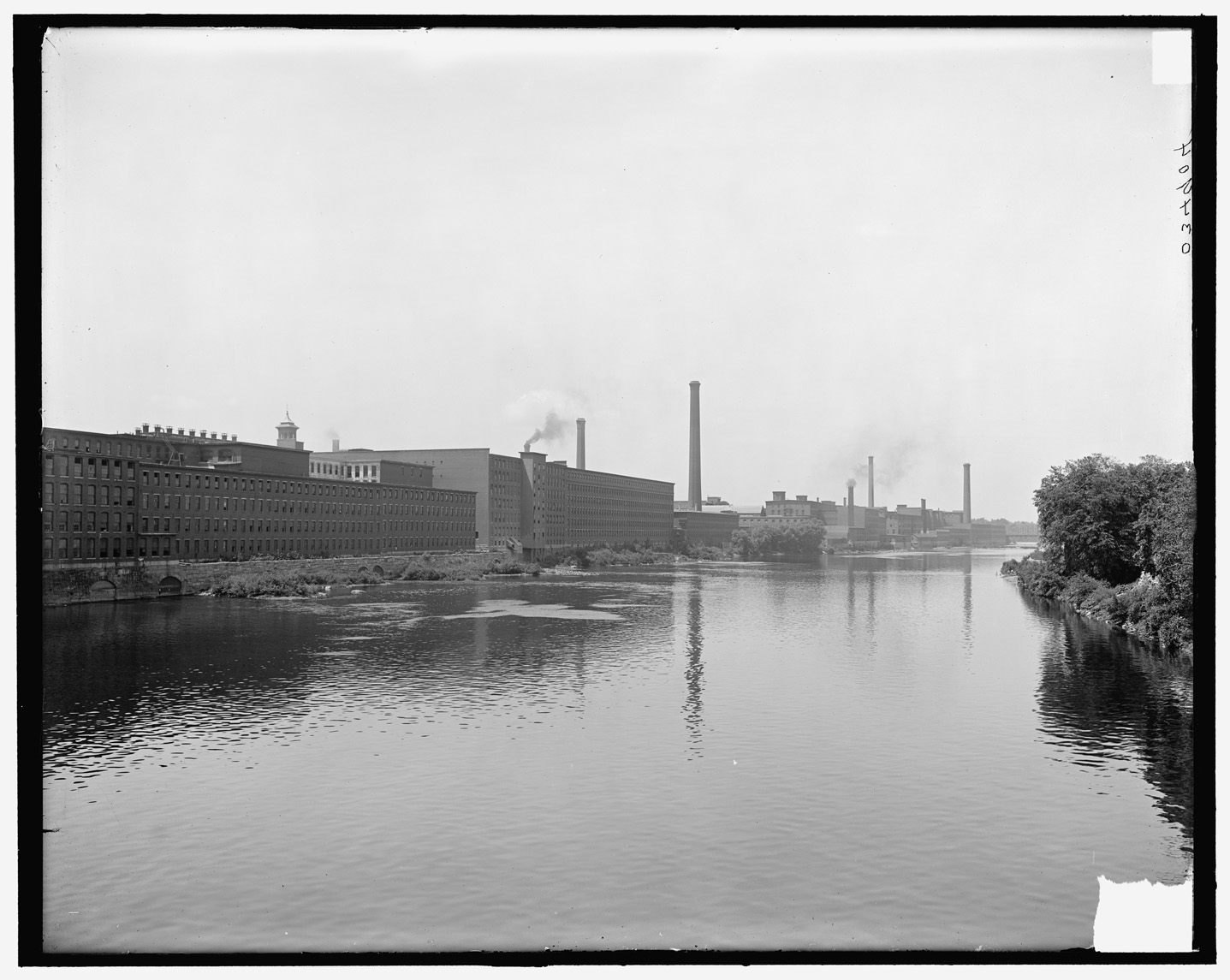 A black and white photograph shows a wide, calm river in its center. On the right, the riverbank is lined with trees. On the left, long industrial buildings about five stories tall run the length of the river. There are many big windows on the buildings and they are flat on top. Smoke stacks are seen in the distance.