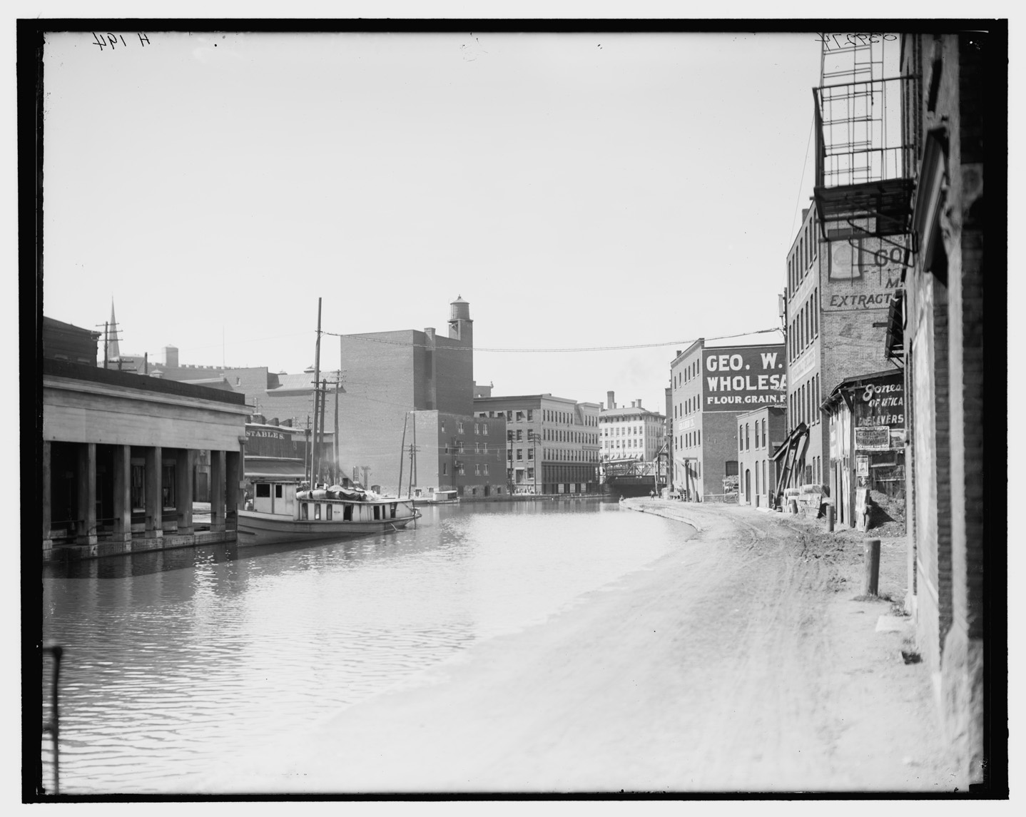 A black and white photograph shows a wide, calm water canal curving through a developed town. On the right side, the water is bordered by sand and then buildings. On the left side, the water rises directly up to buildings. There is a boat tied up to one building.