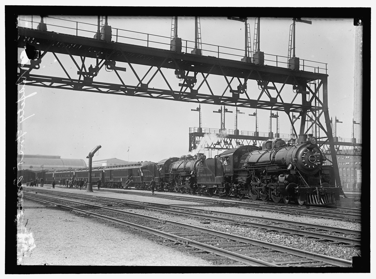 A black and white photograph shows a steam locomotive running on a track. There are several more tracks next to it as well as steel beams overhead. Buildings are in the background. People can be seen getting into and out of the passenger cars attached to the steam locomotive.