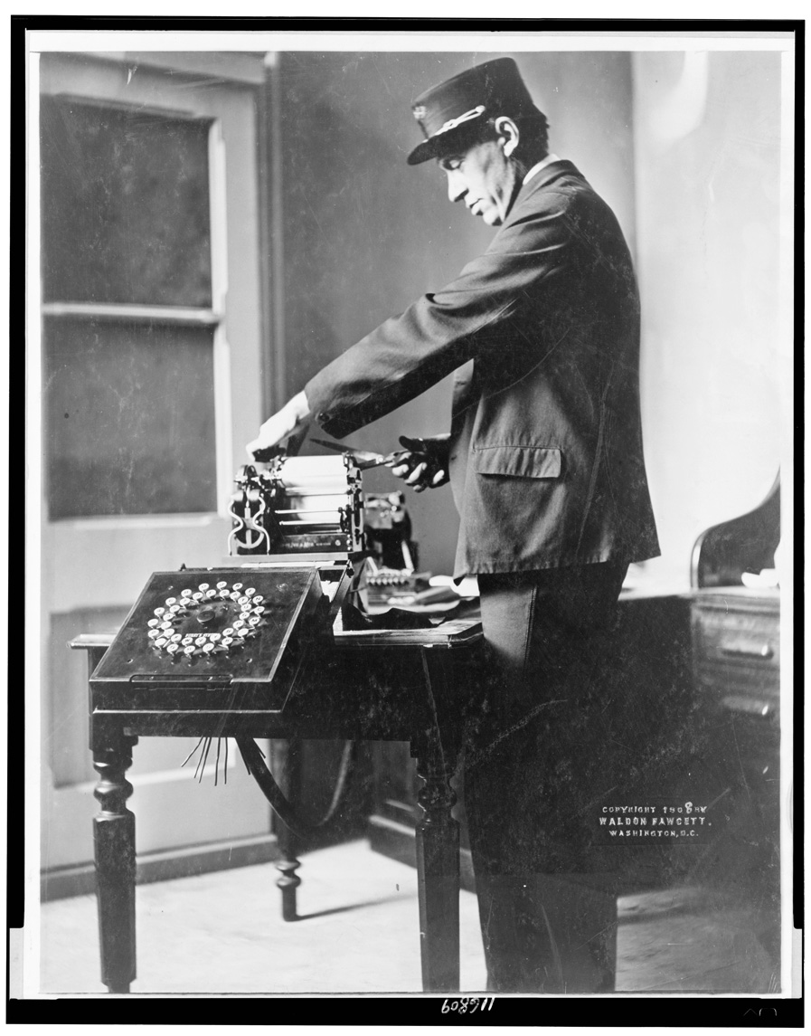 In this black and white photograph, a man stands in a room with a window. He wears a uniform with a cap decorated with gold braid. He stands at a desk, cutting paper from a machine on the desk. The machine has rollers and, on the side, a black square at waist height tilted up. The square is roughly a foot on all sides, and has two circles of buttons, one inside another.