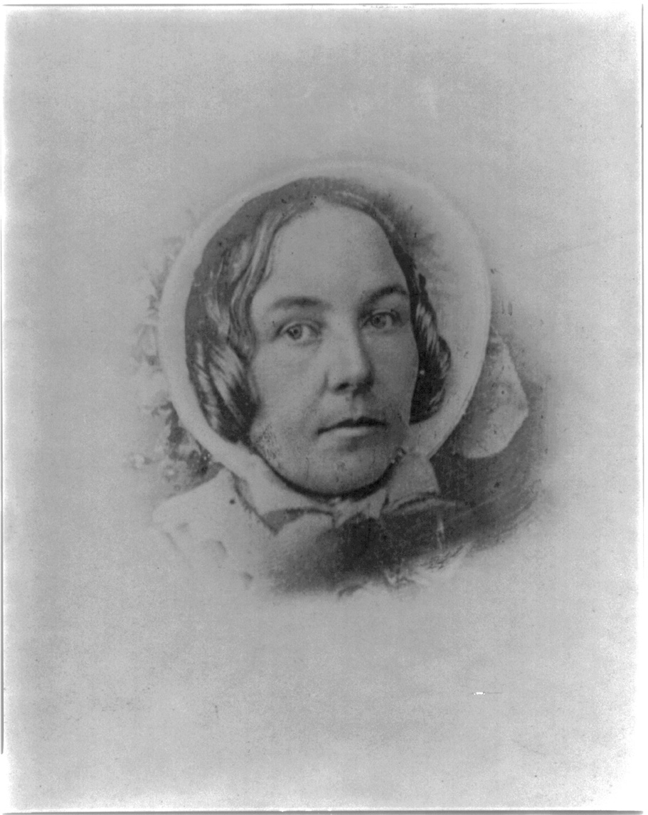 An old black and white photograph shows a woman's head in a bonnet. She is looking to the left and her dark hair comes out from the side of the bonnet next to her face.
