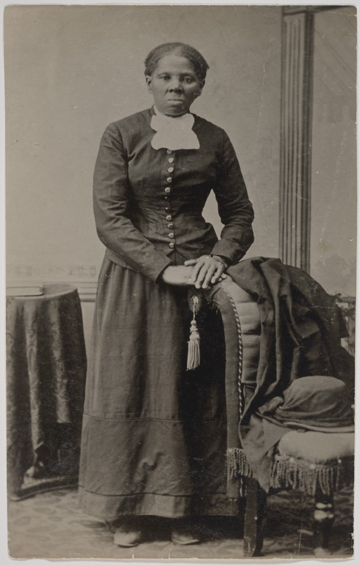A formal black and white photograph shows a woman in dark mid-1800s clothing. Her hair is pulled back and she is not smiling. She is standing in a room between a brocade chair and a small, cloth covered table. She rests her hands on the back of the chair next to her. A jacket and woman's bonnet is on the chair.
