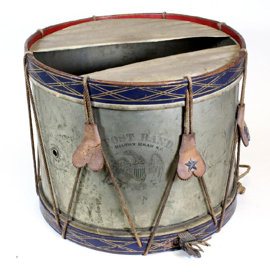 A drum is 13.5 inches high and 17 inches in diameter. The sides are nickel-plated brass engraved with seven broken wreaths. In the center of the wreaths is an eagle with outspread wings and shield; it has lettering above. The lettering reads