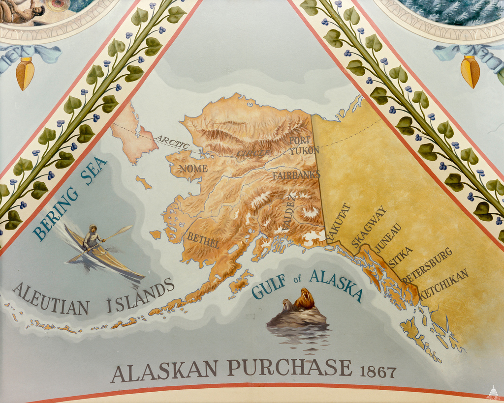 A decorative map shows a close up of the Alaskan purchase connected to western Canada. Alaska is dark orange and shows elevation lines. Canada is dark yellow and bodies of water are various shades of blue. In the water, an Eskimo hunts in a kayak near a seal and walrus. On the map various important towns in Alaska are labeled. The Gulf of Alaska, Bering Sea, and Aluetian Islands are labeled. The map is titled