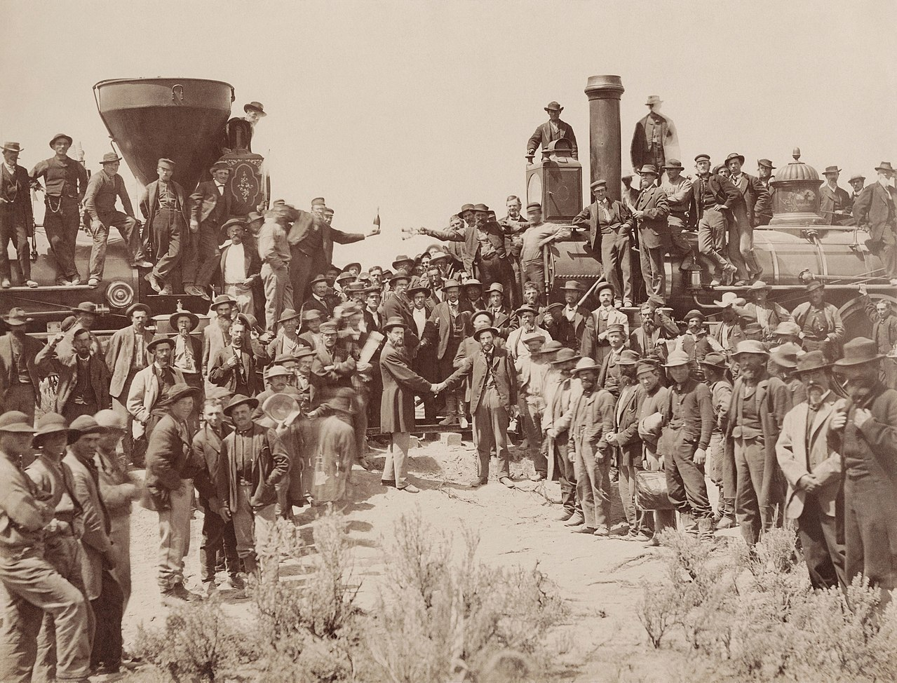 A black and white photograph shows two railroad engines facing each other. The left exhaust pipe is large and shaped like an inverted funnel, while the other exhaust pipe is straight. There are many men in the photograph, standing on the ground, on the engines, and all around. They generally wear hats and working clothes, and some carry shovels or pickaxes. Some are dressed as conductors on trains. Two men in suits stand in the center and shake hands while everyone watches them or faces the camera.