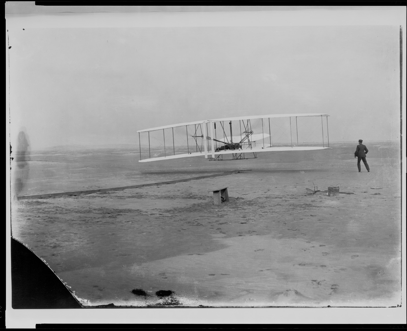 In a black and white photograph, a biplane is shown with two wings stacked on each other. A small engine is seen along with a small body of the plane behind the wings. The plane is on a beach and a man stands watching it, near a wooden bench.