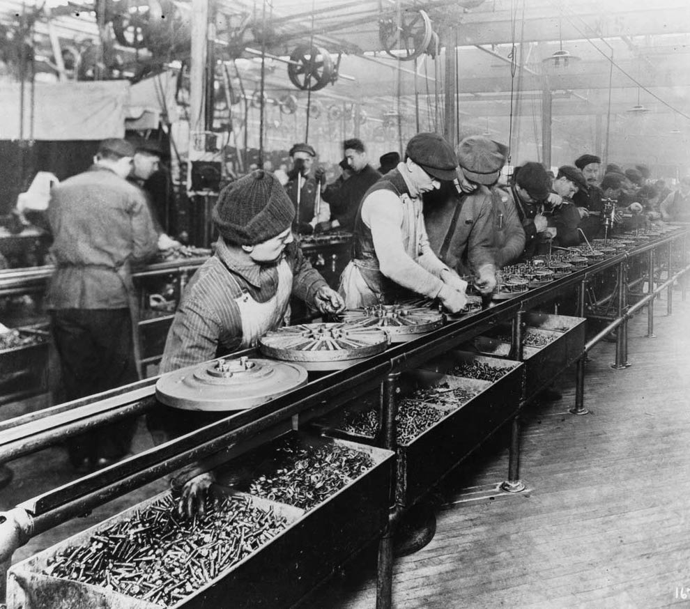 In a black and white photograph, many people work in an assembly line. They are in some sort of factory, and on their line are circular metal pieces, about 18