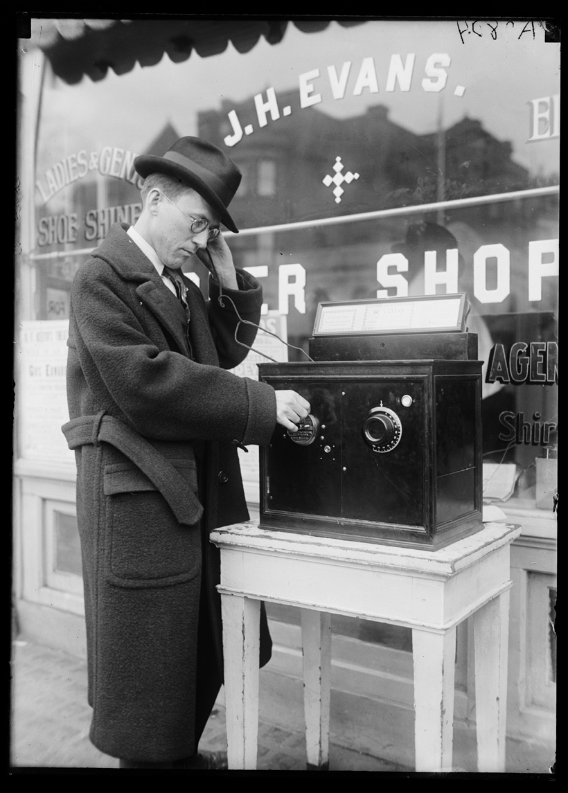 A black and white photograph shows a man in a long coat and hat standing outside a store on a street. Next to him is a table with a large black box on it. On the box are two circles with markings. He is holding something connected with a wire to the black box up to his ear, and touching one of the circles with the other hand. He is looking down at the box..
