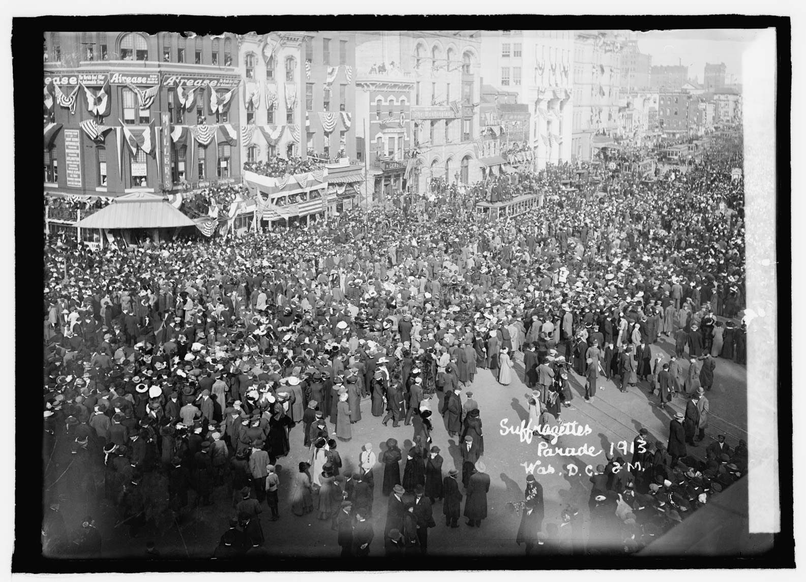 A black and white photograph shows a broad city street filled with people and no cars, seen from above. People generally wear long skirts or coats and hats. The buildings are decorated with half-circle flags draped from windows. Words in cursive in the lower right hand corner read