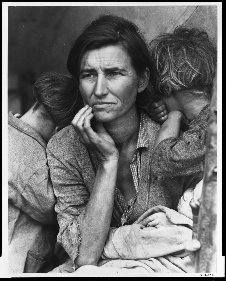 In a black and white photograph, a woman stares off into the distance, looking worried or tired. Her upper torso, shoulders, and head are seen, and her hand is holding her chin. Her hair is loosely pulled back, and she wears a blouse with cardigan. A small child is on either side of her with mussed hair and worn clothing. They have their heads on her shoulders and are facing away from the camera.