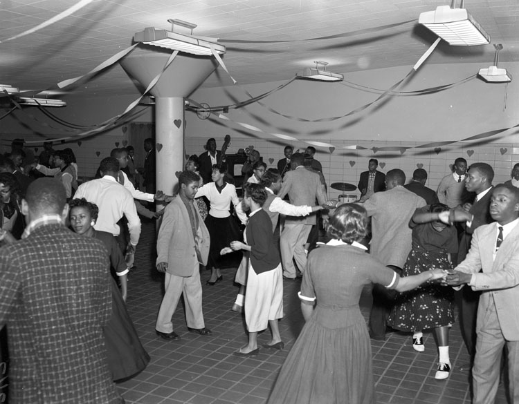 A black and white photograph shows a large room with a pillar and some decorations. Teenangers dance in the room in pairs. Boys wears jackets and ties and girls wears skirts or dresses.