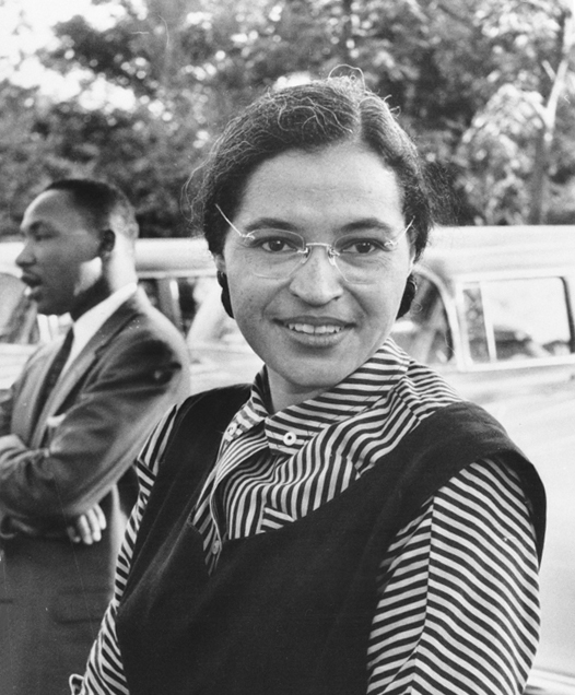In a black and white photograph, a woman looks at the camera with a small smile. She has glasses, a striped blouse with a vest, and her hair pulled back. In the background, there is a car, and a man with a suit and tie, who is talking with his arms crossed.
