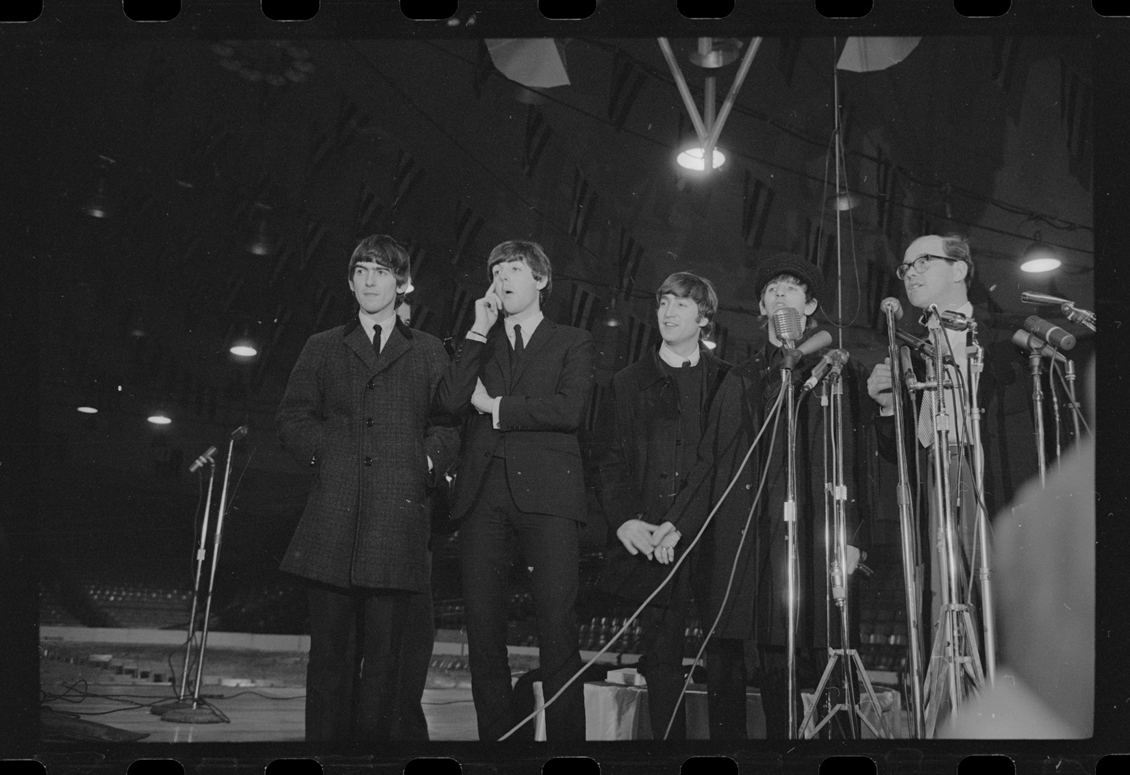 Five men in suits and jackets stand in a line facing the viewer in a black and white photograph. In front of the two rightmost men are many microphones on stands. All the men are looking off to the left, and are standing in a large room with flags hanging from the ceiling.