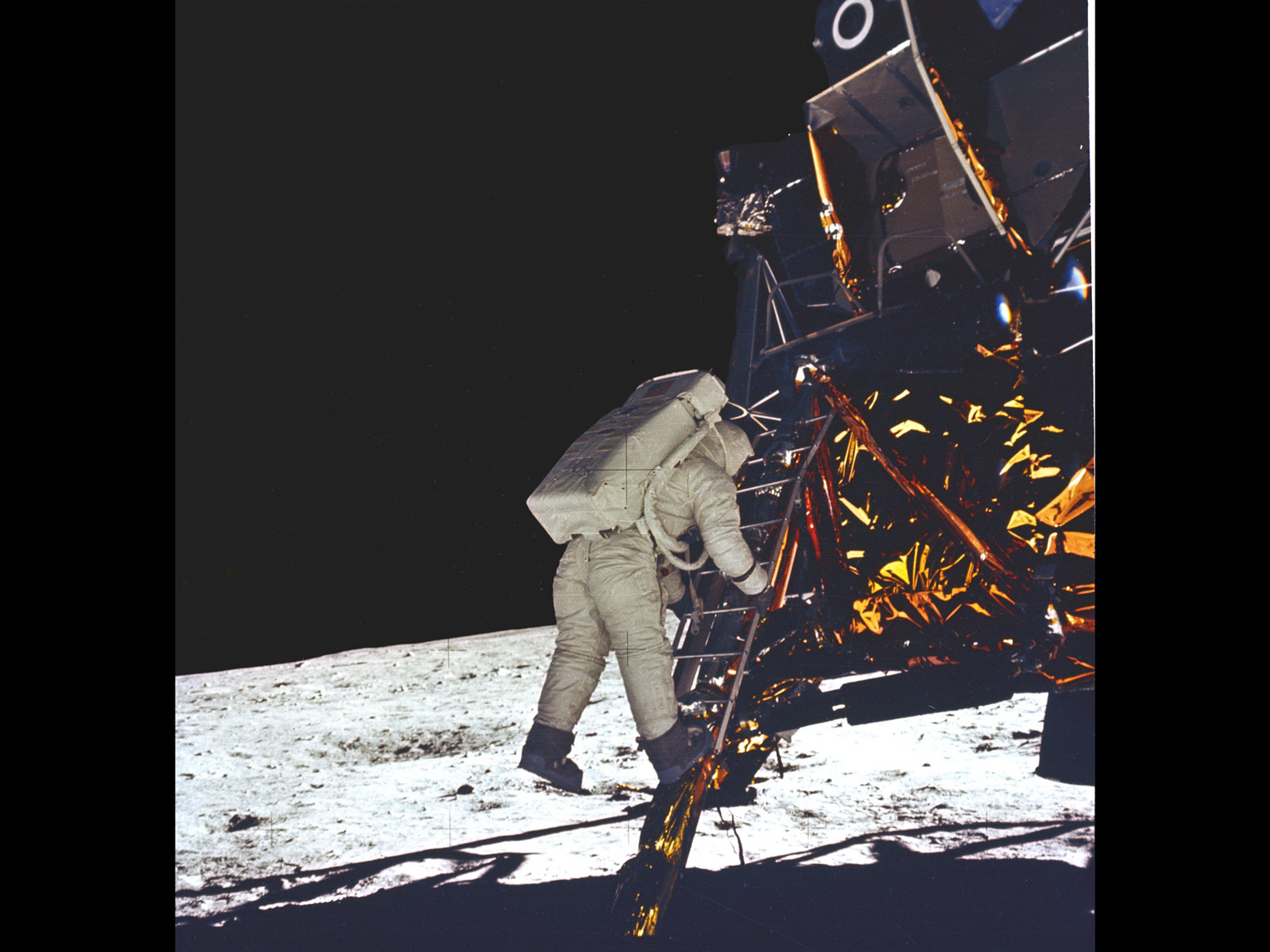 In a color photograph, an astronaut with a white spacesuit and large backpack descends a ladder. He is leaving a small spaceship and stepping down to walk on the moon.