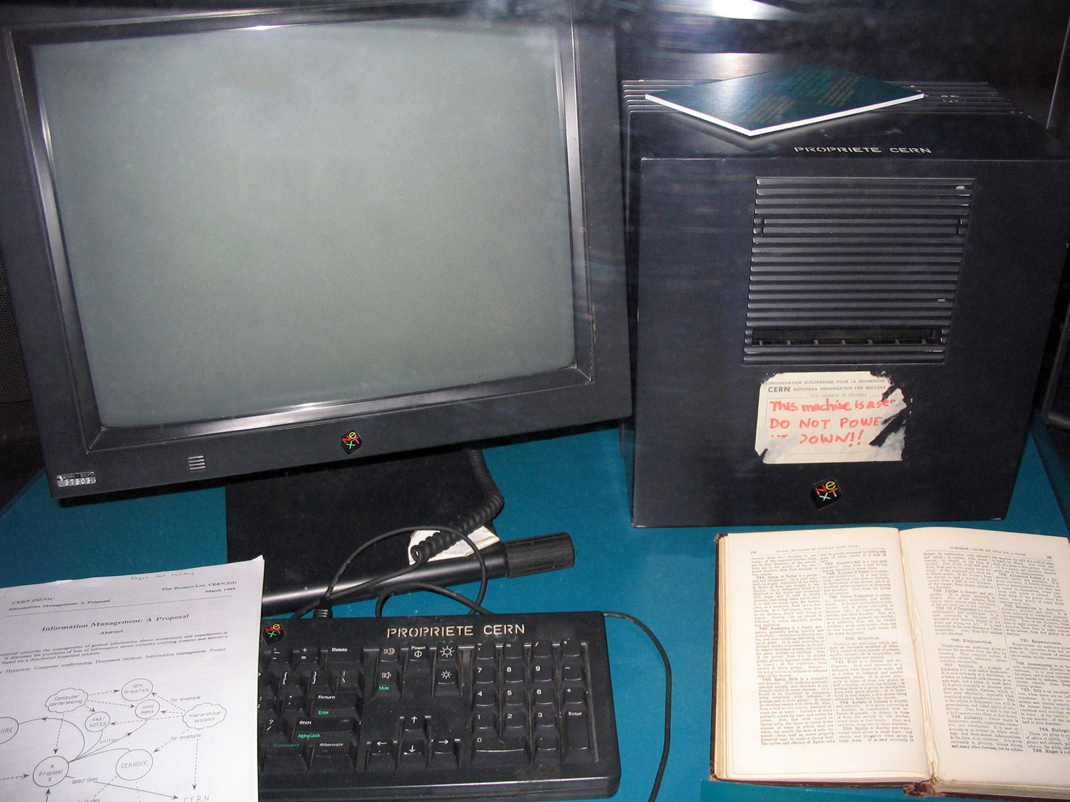 A color photograph of a black computer monitor is seen. It sits on a blue desk with part of a keyboard, covered by a piece of paper with typing, visible below. On the keyboard reads
