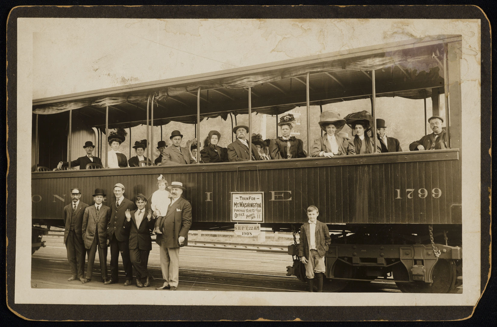 Photo of train with passengers posing next to it and passengers seated inside